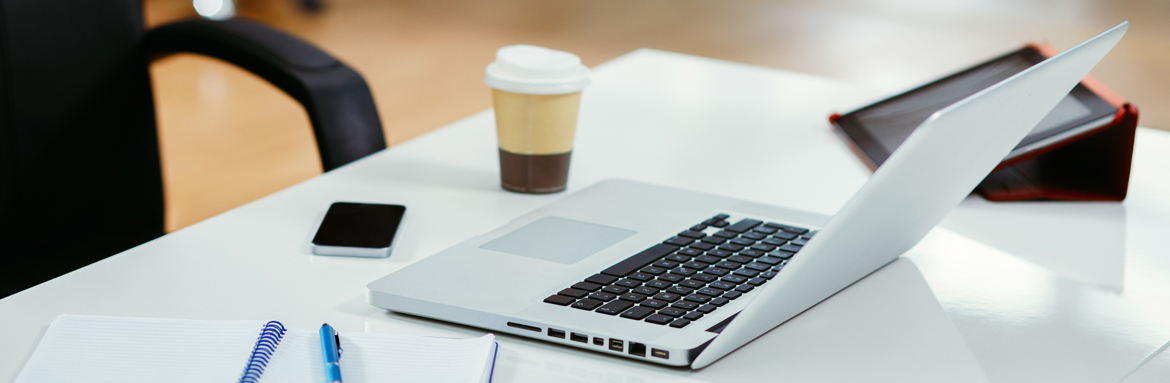 A desk with a laptop, tablet, smartphone, notebook and coffee cup.